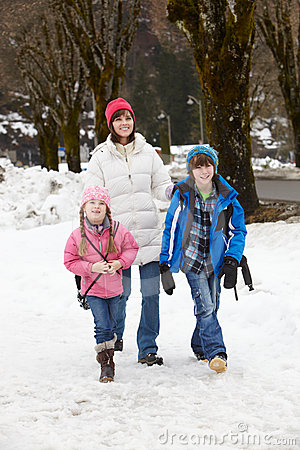 Mother Walking Two Children To School In Snow