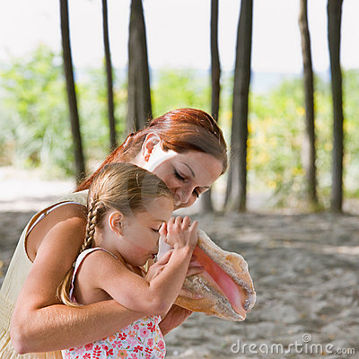Mother watching daughter blow into seashell