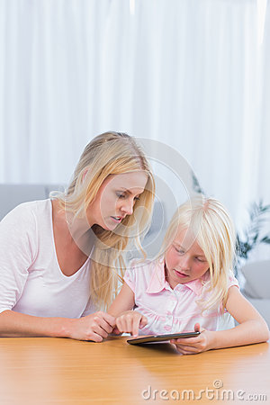 Mother watching her daughter using digital tablet
