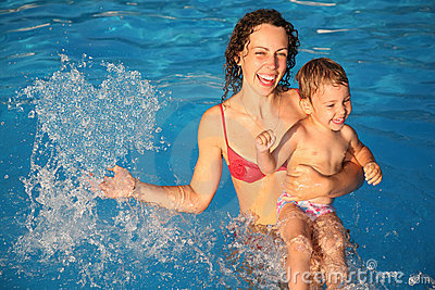 Mother in water with child makes heart with drops