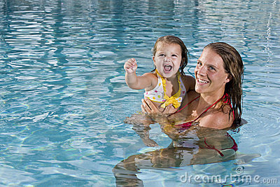 Mother and young daughter enjoying swimming pool