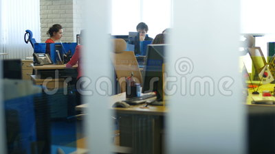 Motion along Room Glass Office Workers Consult Clients. KAZAN, TATARSTAN/RUSSIA - JUNE 08 2015: Camera moves about room through glass with office workers