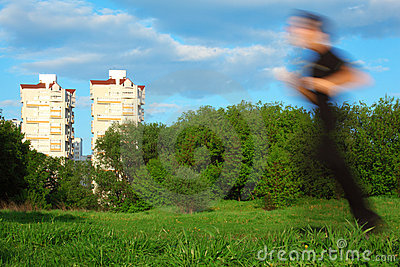 Motion blur man running in park and buildings