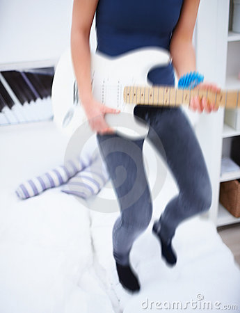 Motion blur of woman playing guitar on bed
