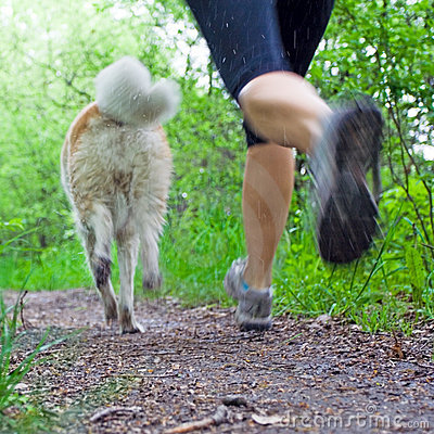 Motion blur of woman running with dog in forest