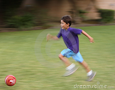 Motion blurred boy with soccer ball