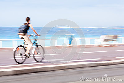 Motion blurred cyclist going fast on a city bike lane