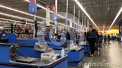 Motion der Leute, die am Check-out-Schalter im Walmart-Laden Lebensmittel bezahlen stock footage