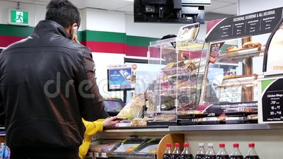 Motion of people line up for paying food at 7 eleven check out counter. In Coquitlam BC Canada