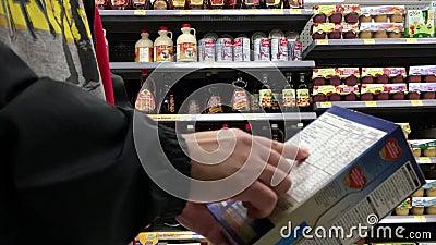 Moto dell'uomo che prende l'avena di Quaker e che legge ingrediente del prodotto video d archivio
