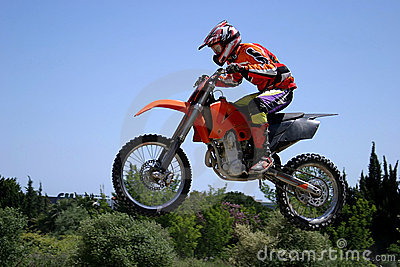 Moto X Motorbike jumping through the air on a hot sunny day with blue sky