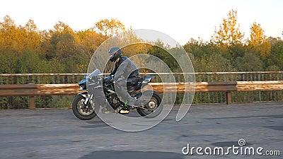 Motociclista con casco y motocicleta deportiva moderna en el viejo puente oxidado de la carretera Joven corriendo su almacen de video