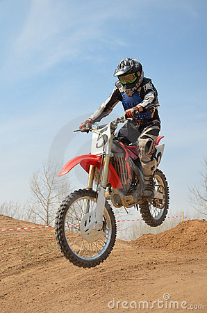 Motocross motorbike racer performs a jump