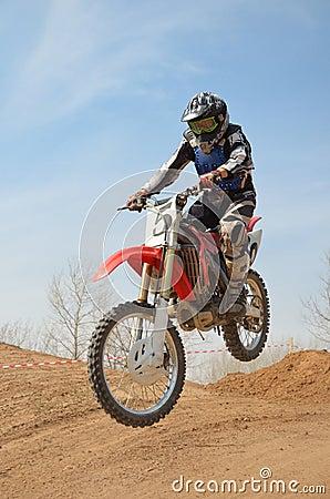 Motocross motorbike racer performs a jump