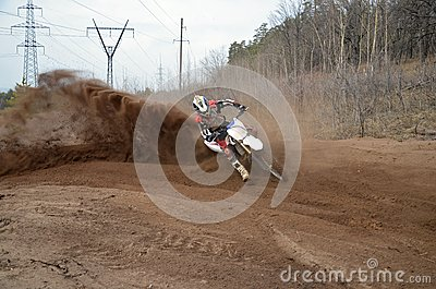 Motocross racer moves along sandy parapet turning track