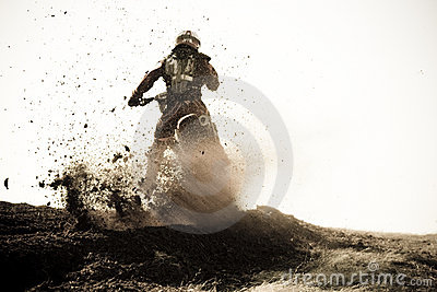 Motocross racer roosts dirt berm on track.