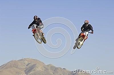 Motocross Racers Performing Stunt In Midair Against Blue Sky