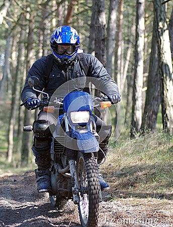 Motocross rider in dirt path