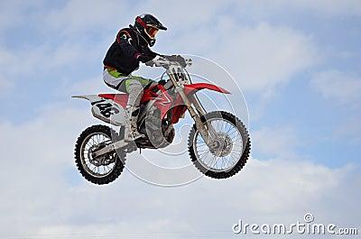 Motocross rider jump, blue sky