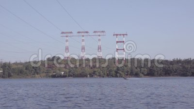 Motor boat floats on the river against the background of high-voltage power transmission towers. Daytime. Dnepro river. Zaporozhe, Ukraine stock footage