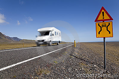 Motor Home Driving On Road With Danger Sign