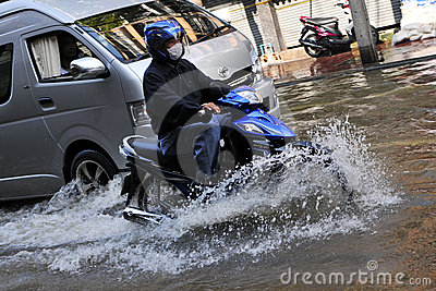 Motorbike Rider Navigates a Flooded Street Editorial Photo