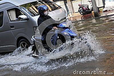 Motorbike Rider Navigates a Flooded Street Editorial Photo