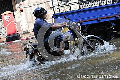 Motorbike Rider Navigates a Flooded Street Editorial Image