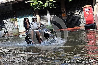 Motorbike Rider Navigates a Flooded Street Editorial Stock Photo