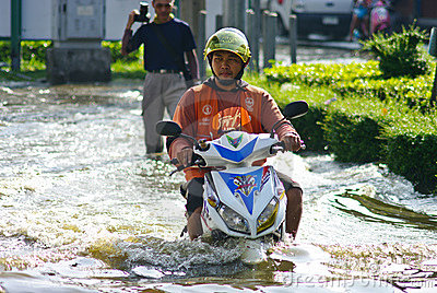 Motorbike run through flooded road Editorial Stock Photo