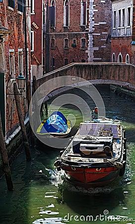 Motorboot auf einem kleinen venetianischen Kanal Redaktionelles Stockbild