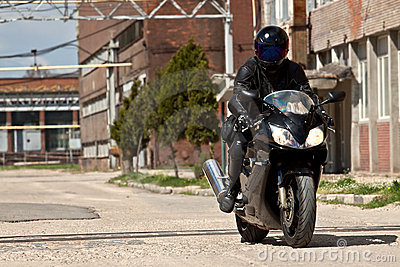 Motorcycle rider with complete black outfit