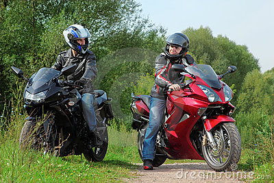 Motorcyclists standing on road looks on each other
