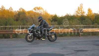 Motorradfahrer fahren auf dem modernen Motorrad auf der alten rostigen Autobahn schnell auf dem Helm Der junge Mann rennt stock video