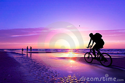 Mountain biker on beach and su