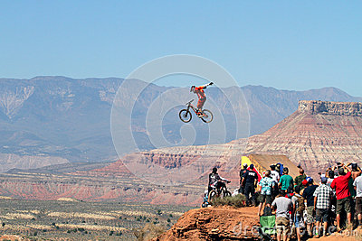 Mountain biker jumps cliff and crowd watches Editorial Photo