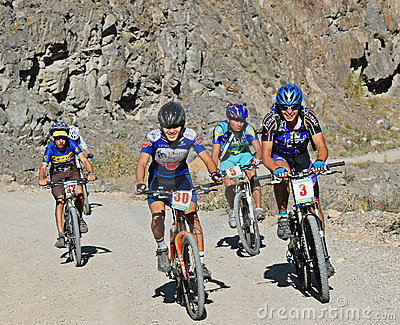 Mountain bikers uphill on rural road in rocks Editorial Photo