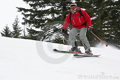 Mountain man skier rolling down the slope