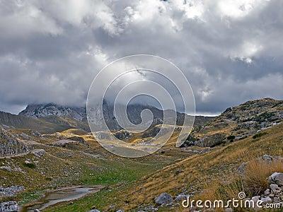 Mountain peak hidden by low nimbus clouds.