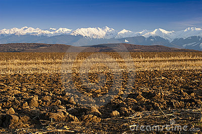 Mountain range snow peaks plowed field