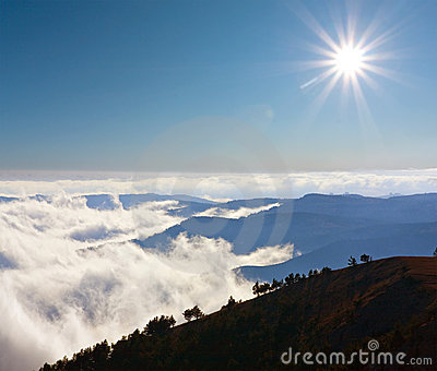 Mountain s scene with sun over clouds