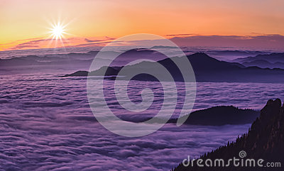 Mountain sunset above clouds