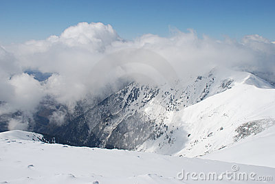 Mountain winter slope in clouds.
