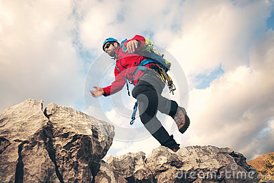 Mountaineer jumps over rocks in mountin Stock Photo