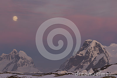 Mountains of the Antarctic Peninsula in the red sunset in the mo