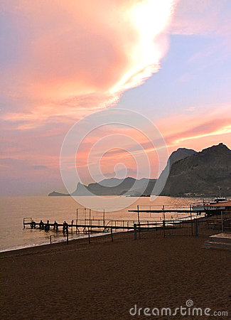 Mountains, the sea, sandy beach at sunset