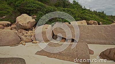 Mouvement le long de Heap Rocks on Sand Beach à Hill Foot banque de vidéos