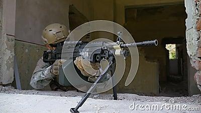 Mouvement lent d'un soldat armé dans le camouflage avec le fusil de mitrailleuse regardant hors de la fenêtre banque de vidéos