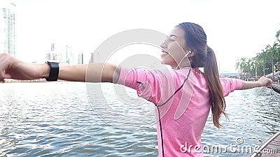 Mouvement lent - la belle femme asiatique dans des équipements de forme physique emploient un smartwatch pour écoutent la musique clips vidéos