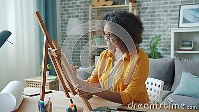 Movimento lento da jovem artista afro-americana pintando em casa na mesa filme